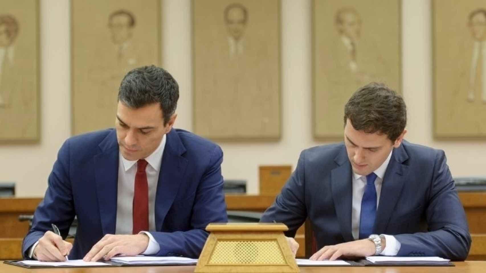 Sánchez y Rivera han inclinado la cabeza, apoyado la misma mano e utilizado el mismo bolígrafo durante la firma