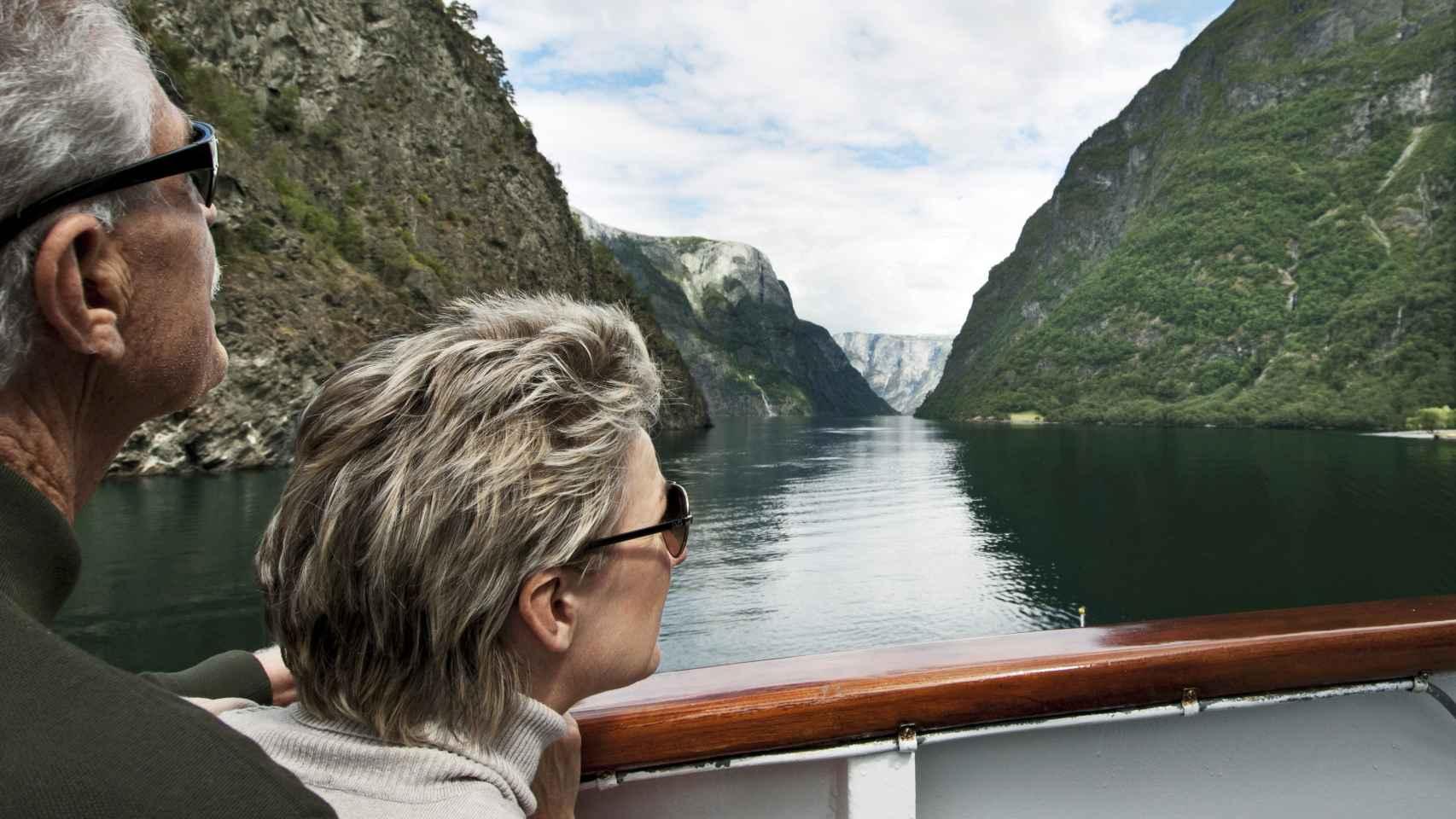 Pasajeros contemplan el escenario que ofrecen los fiordos.