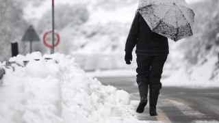 Una mujer camina entre la nieve por una carretera de Lugo