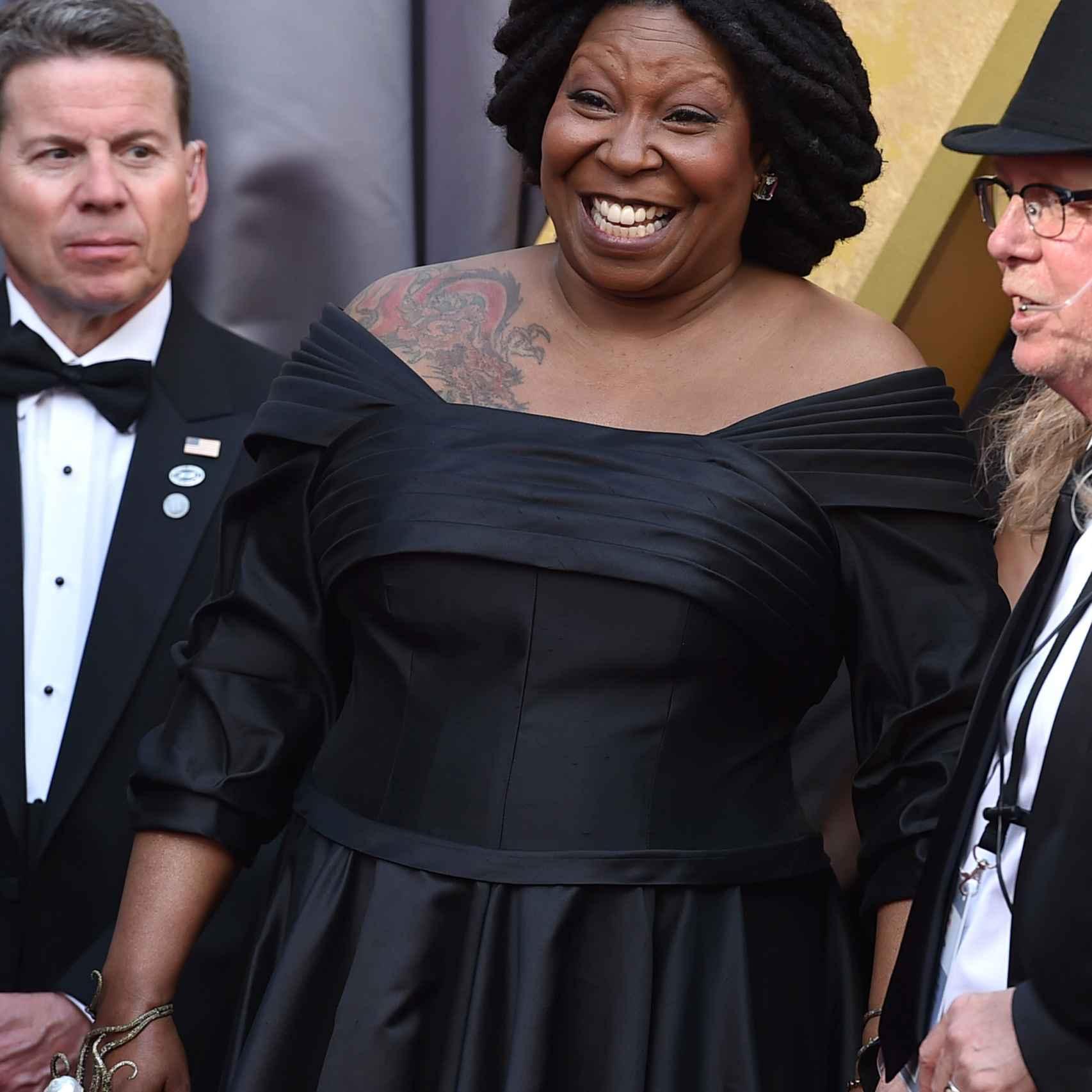Whoopi Goldberg lleva un vestido negro nada favorecedor. El tatuaje en el hombro anti alfombra roja