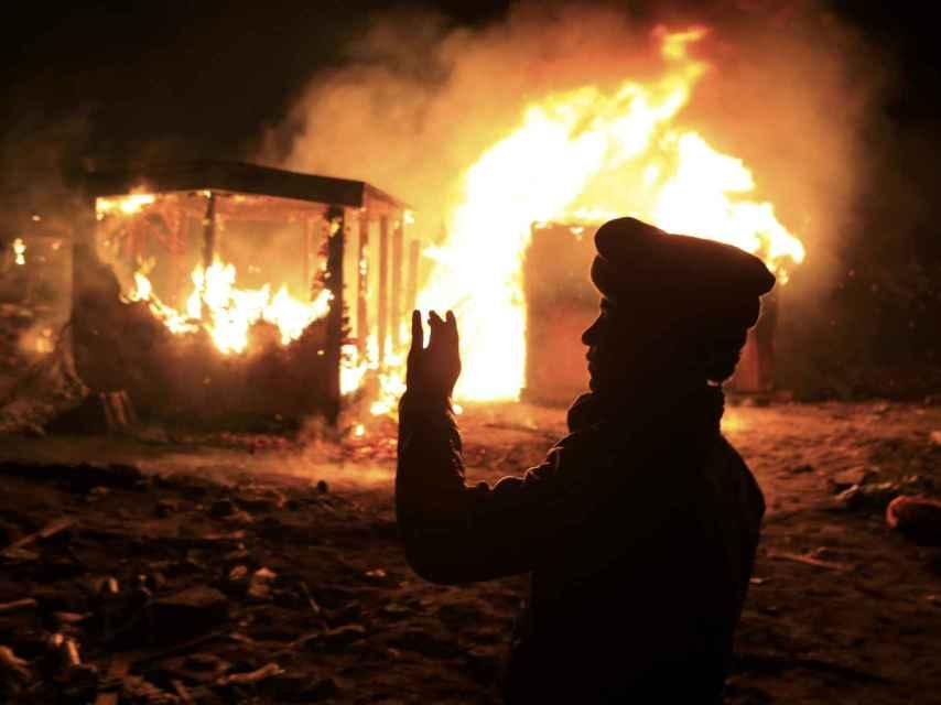 Un refugiado contempla cómo arde una de las cabañas