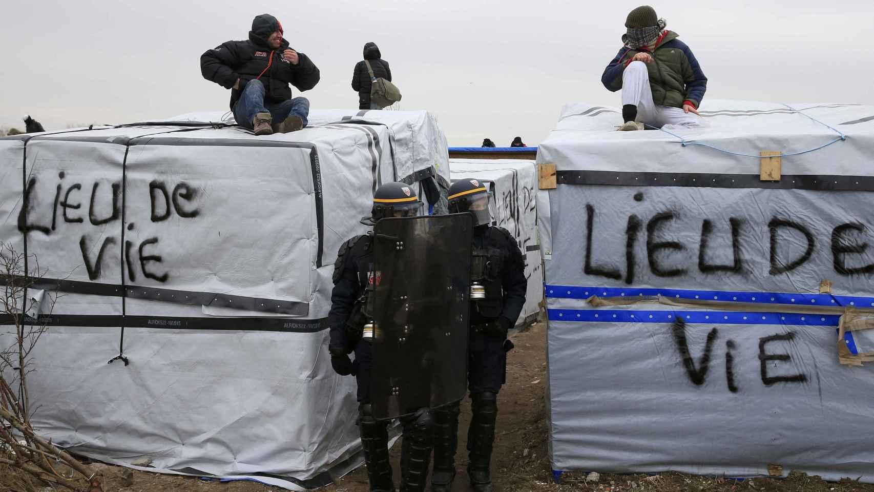 Un grupo de refugiados protesta encima de sus cabañas por el desalojo