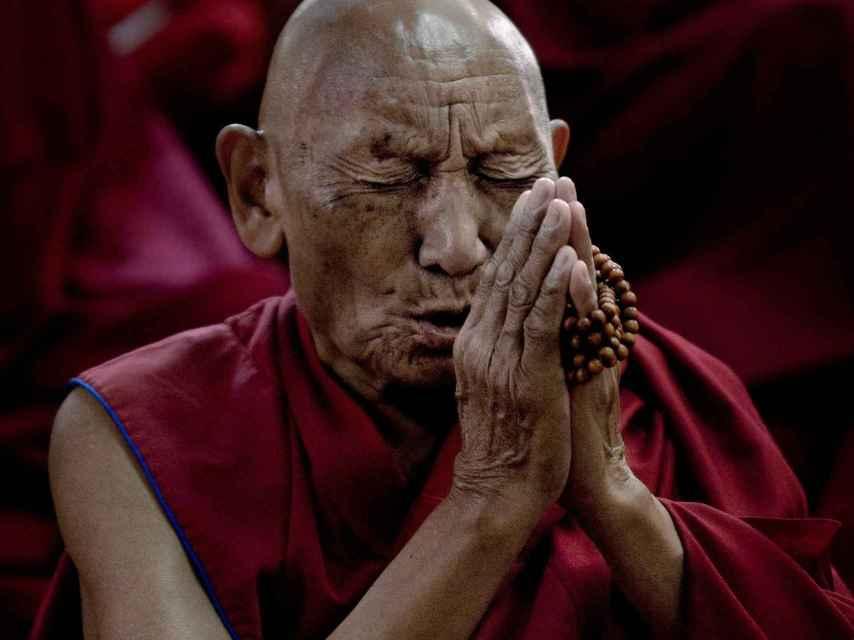Palden Gyatso estuvo 33 años preso en las cárceles chinas de Tíbet. Escapó cruzando el Himalaya a pie y denunció las torturas sufridas en su libro 'Fuego bajo la nieve'. En la imagen, reza en el monasterio de Namgyal Monastery, en Dharamsala,  por sus compatriotas inmolados (143 hasta la fecha).