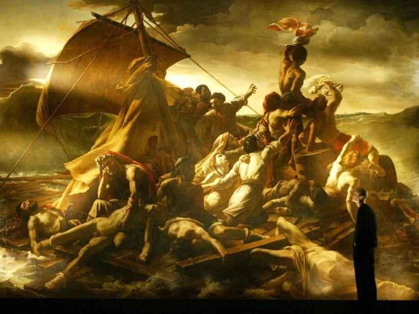 Un hombre observa La basla de la Medusa, de Théodore Géricault.
