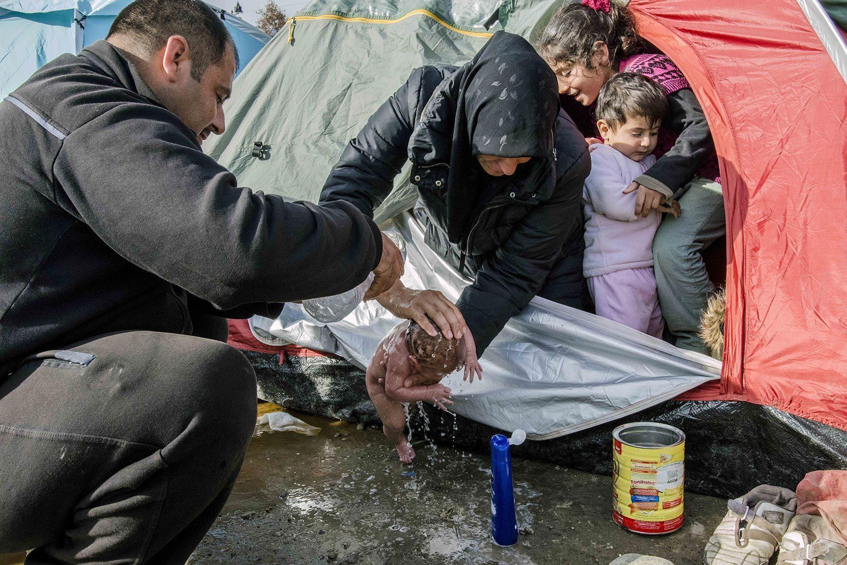 Los padres de Bayan la bañan en el campo de Idomeni.