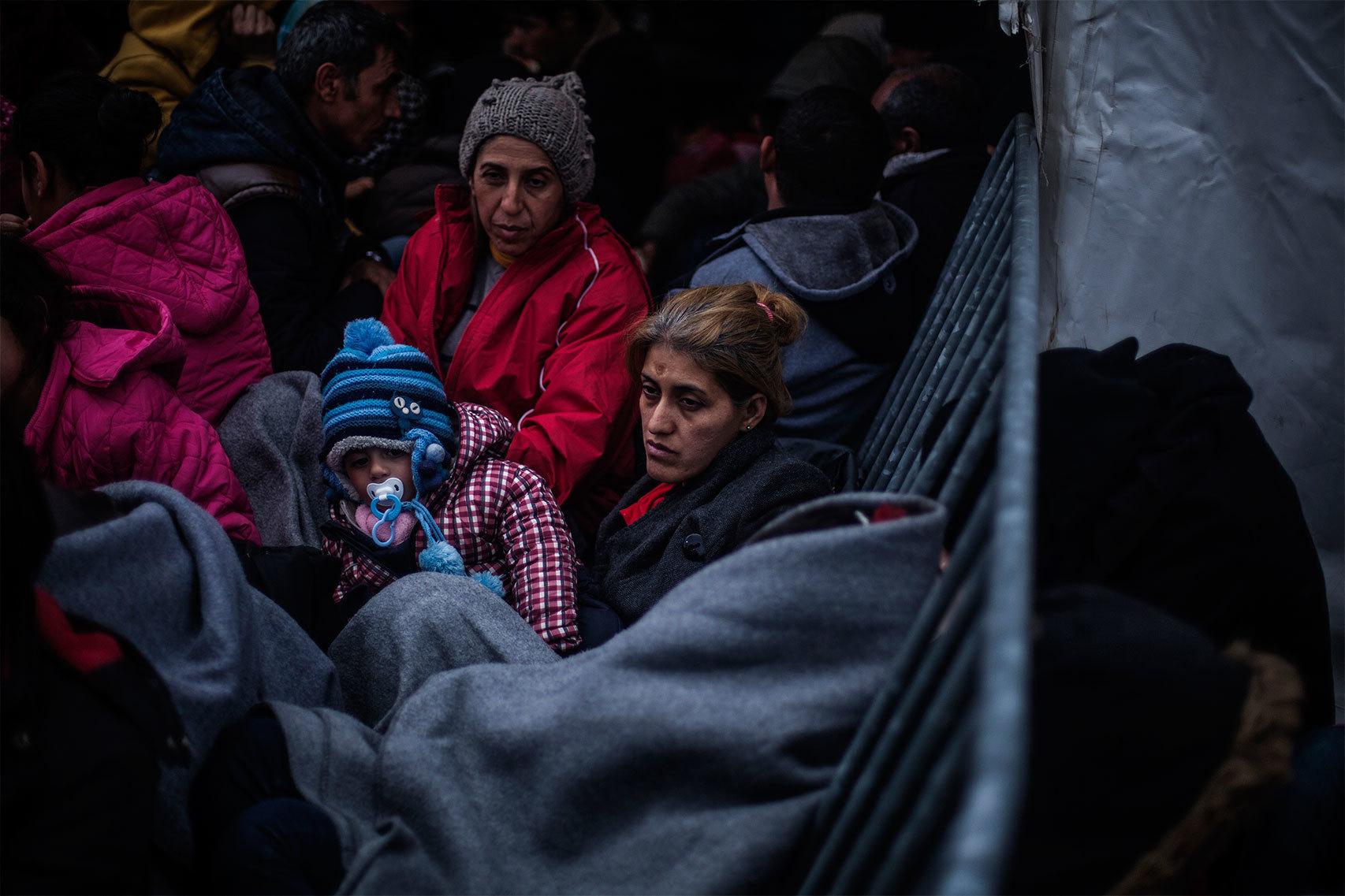 Una mujer espera con su bebé cerca del paso fronterizo de Idomeni.
