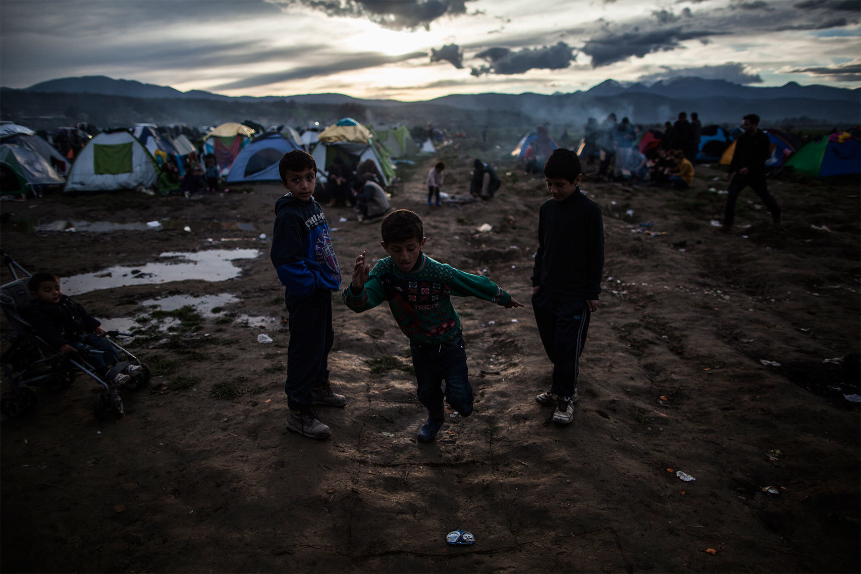 Niños juegan en medio del barro.