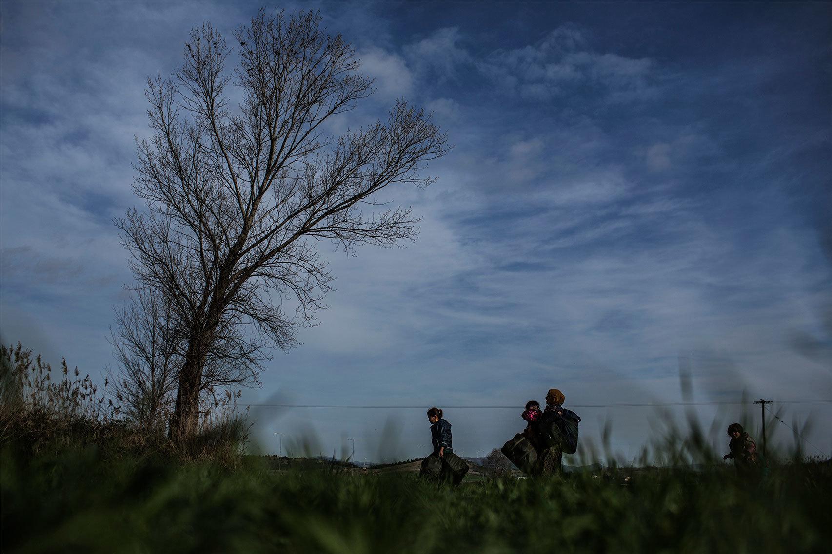 Una mujer con su bebé a cuestas en medio del campo.