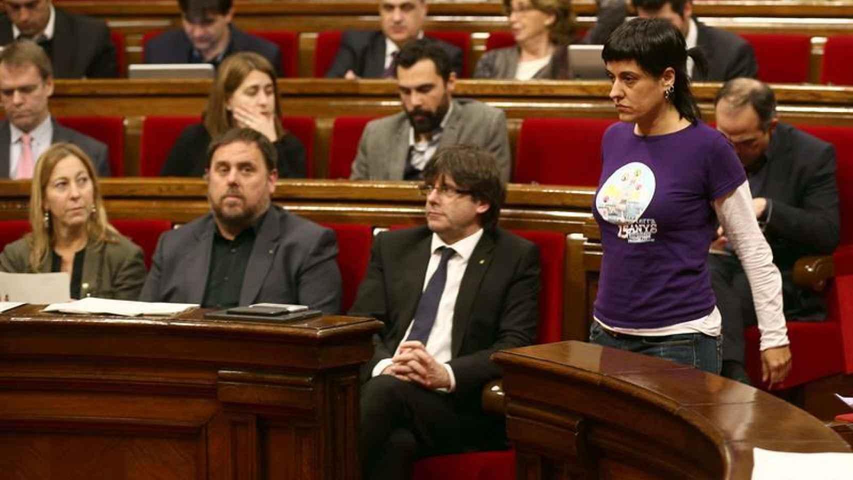 La diputada de la CUP, Anna Gabriel pasa ante el presidente de la Generalitat, Carles Puigdemont