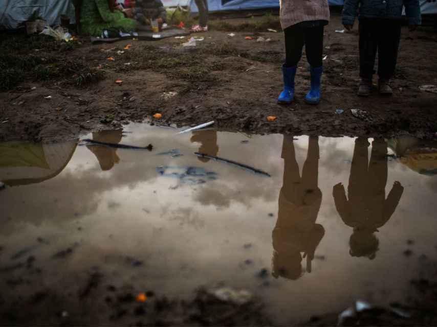 Niños reflejados en un charco en Idomeni.