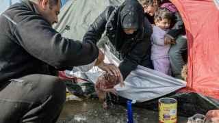 Los padres de Bayan la bañan frente a su tienda de campaña en Idomeni.