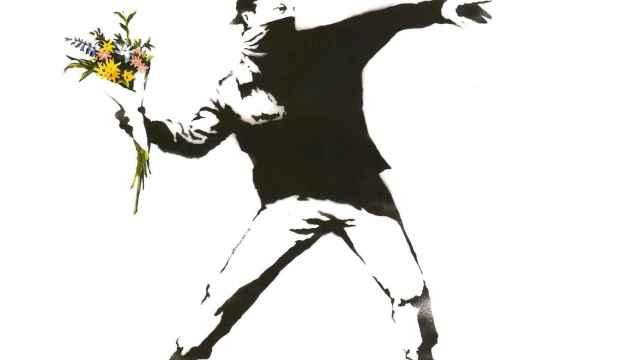 Un activista lanza un ramo de flores en una de las obras más populares de Banksy