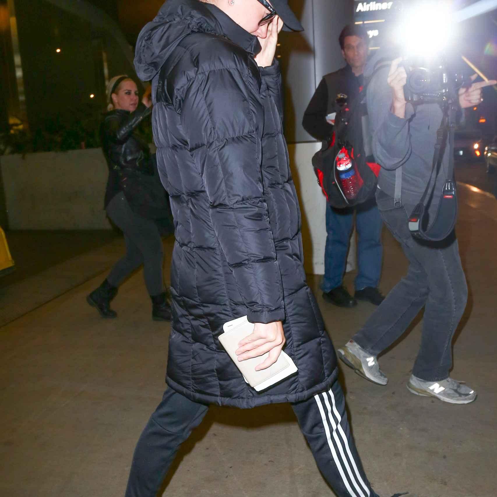 Katy Perry intenta ocultarse de los fotógrafos en el aeropuerto