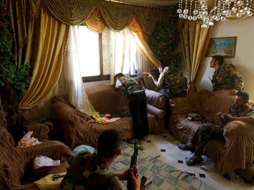 Un rebelde dispara desde una casa en Alepo.