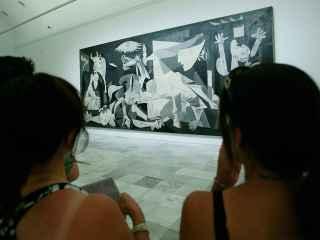 Dos jóvenes observan el Guernica en el Reina Sofía.