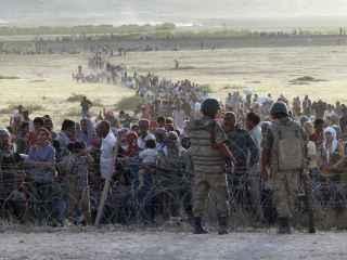 Ciudadanos sirios aguardan junto a la frontera turca.