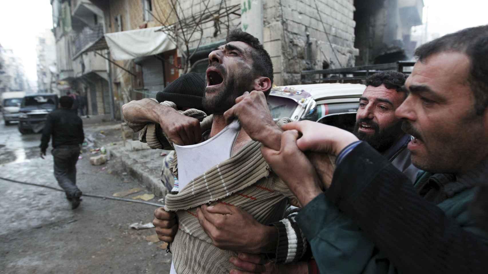 Un padre lamenta la muerte de sus hijos tras un bombardeo en Alepo.