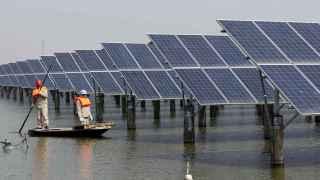 Operarios revisan paneles solares en China.