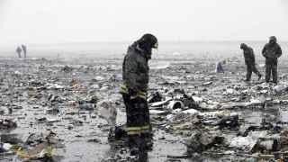 Un bombero busca las cajas negras entre los restos del avión.