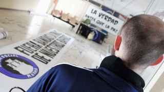 Un 'militante' del Hogar Social Madrid frente a una pancarta: La verdad antes que la paz.