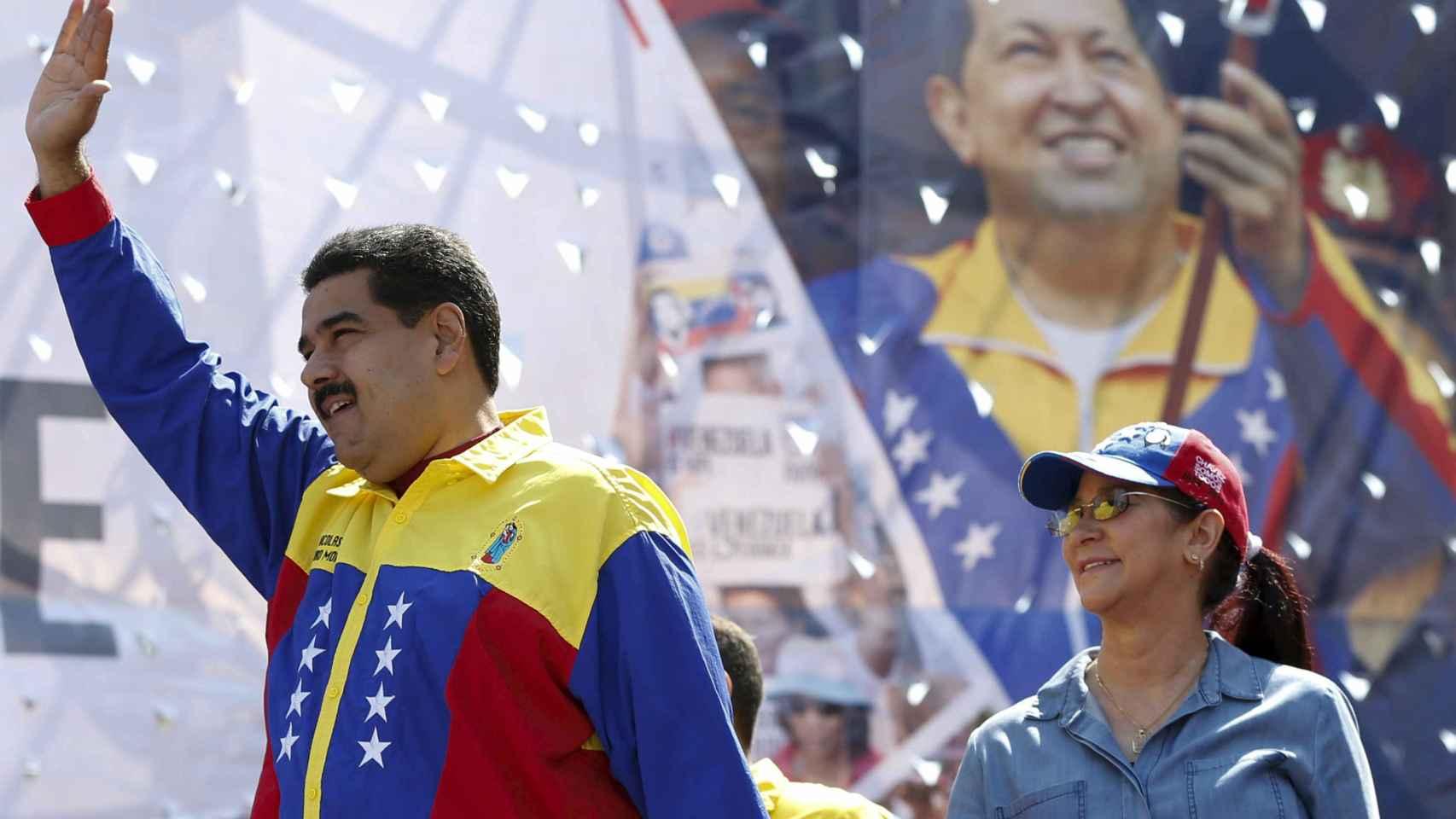 Nicolás Maduro y su mujer ante una imagen de Hugo Chávez