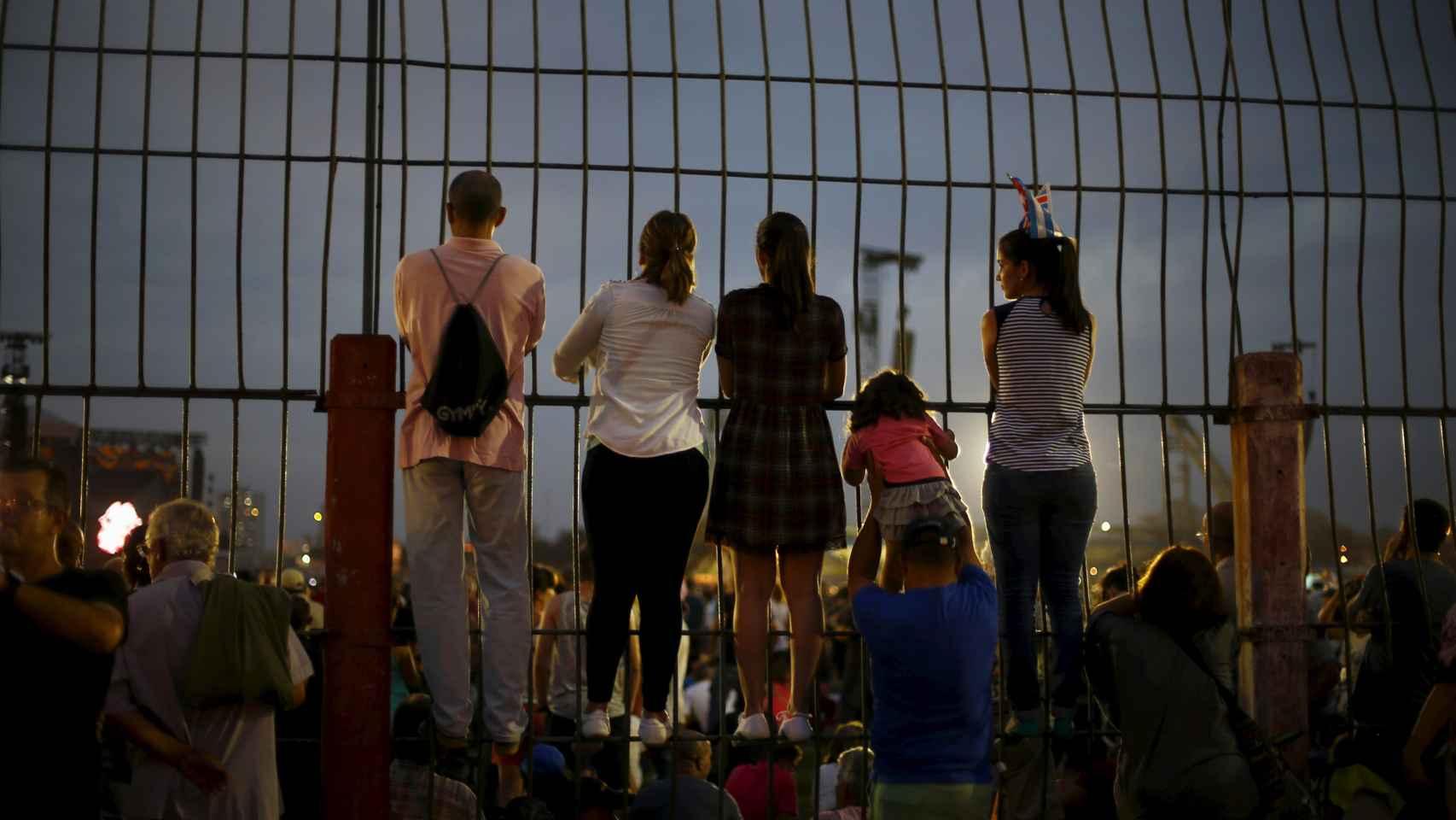 Varios fans se encaraman a una valla para poder ver el espectáculo