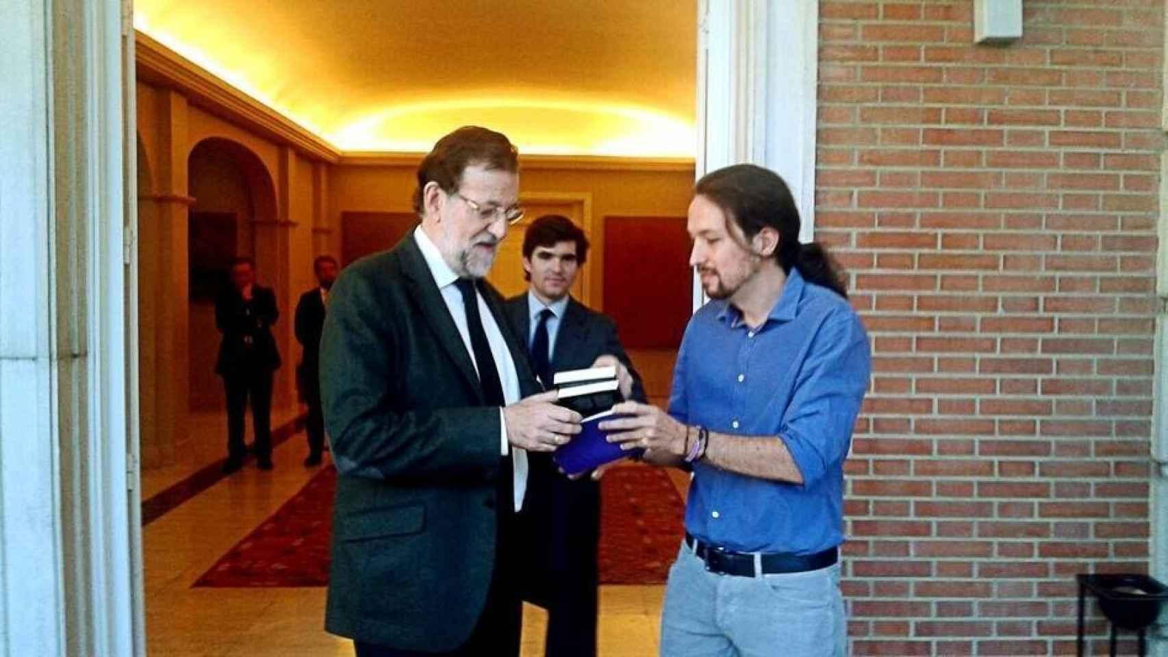Pablo Iglesias regala un libro a Mariano Rajoy.