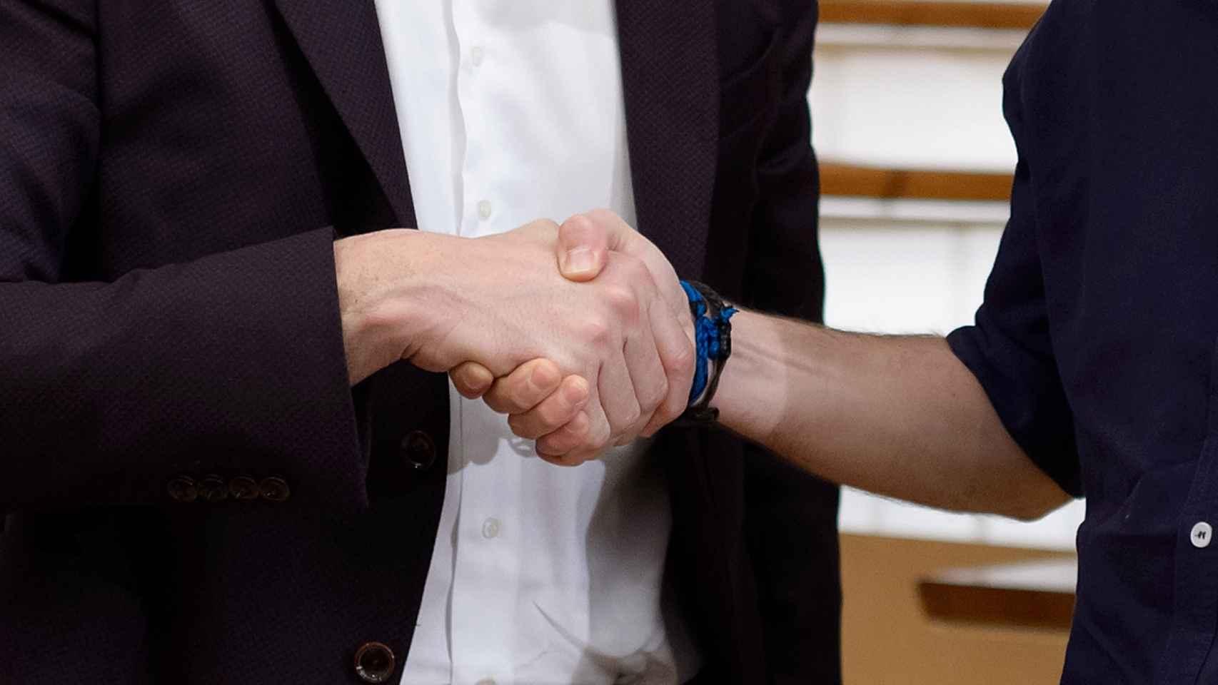 Pedro Sánchez y Pablo Iglesias estrechan sus manos.