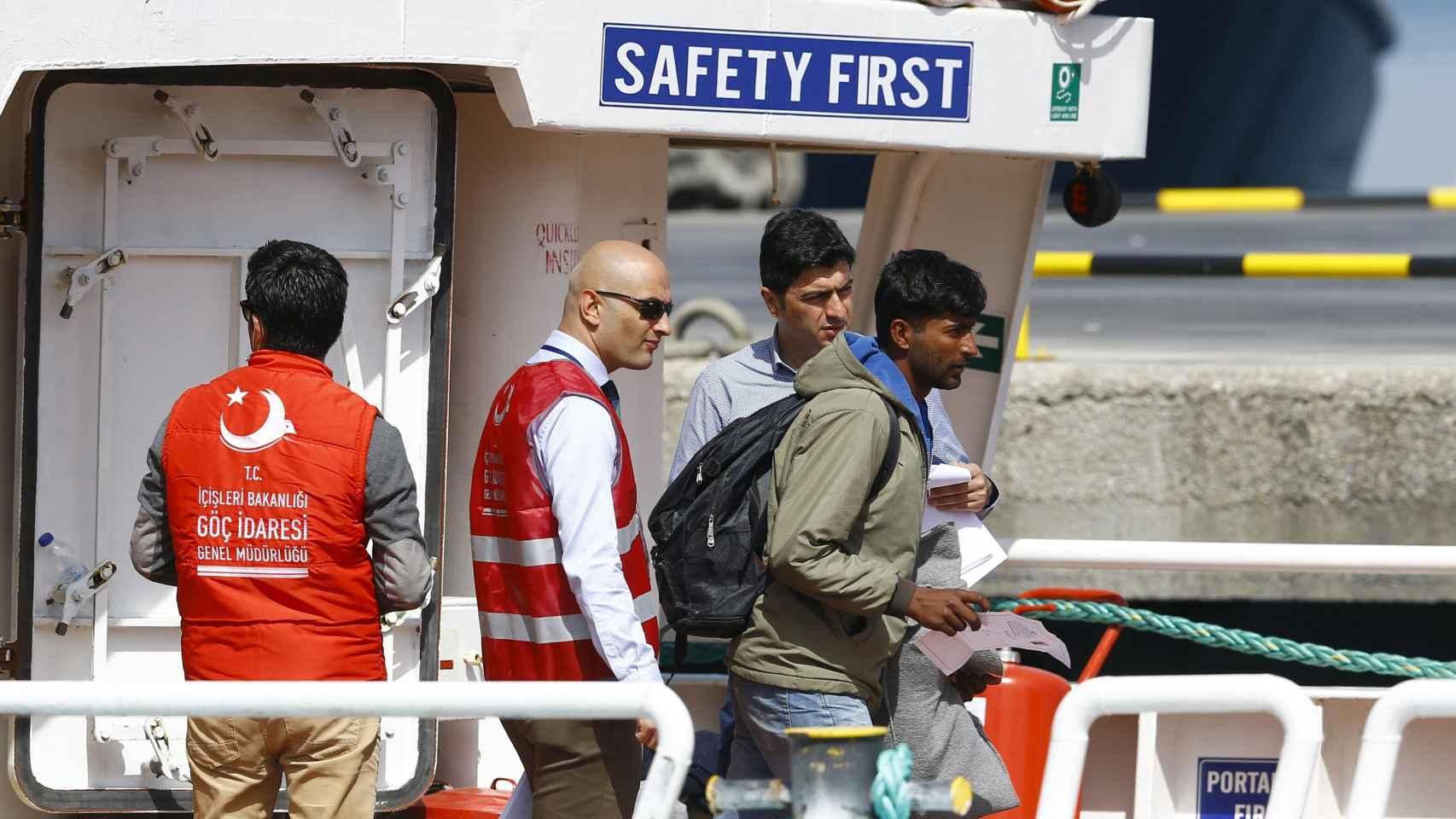Un migrante deportado a Turquía, bajo una señal de la seguridad, primero.
