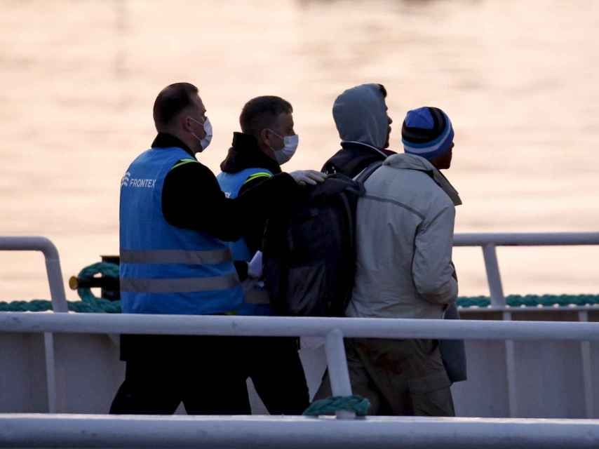 Agentes turcos escoltan a los primeros migrantes deportados bajo una señal de la seguridad, primero.