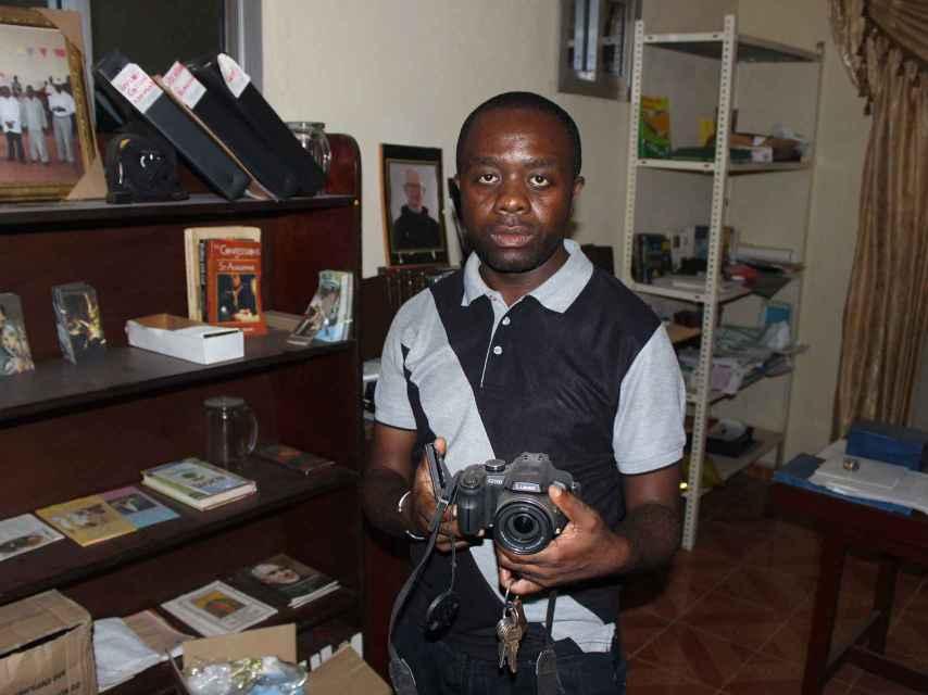 El padre Nestor Banboye muestra la cámara de Manuel.