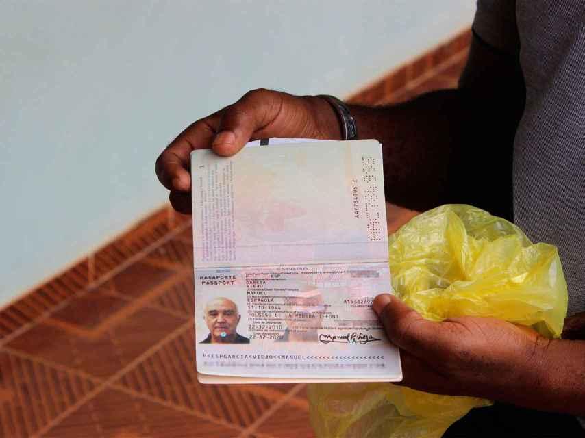 Un sacerdote muestra el pasaporte de Manuel García Viejo.