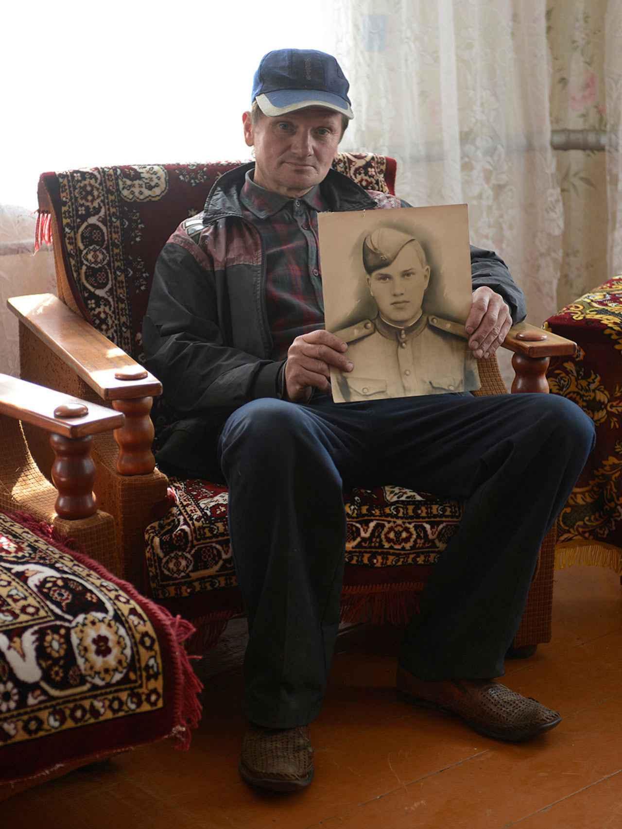 Sergey posa con un retrato de su padre, muerto por la radiación.