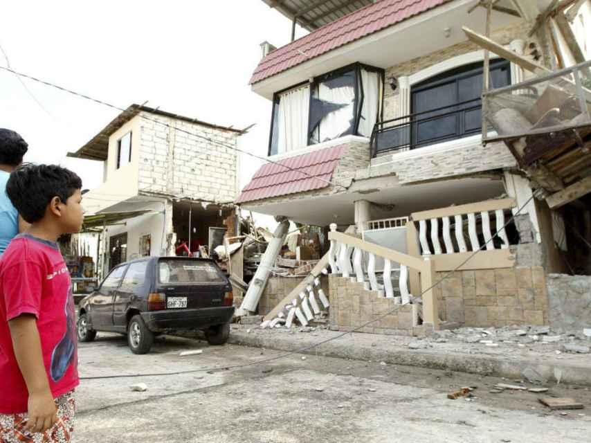 Un niño observa un edificio dañado en el barrio de Manta.