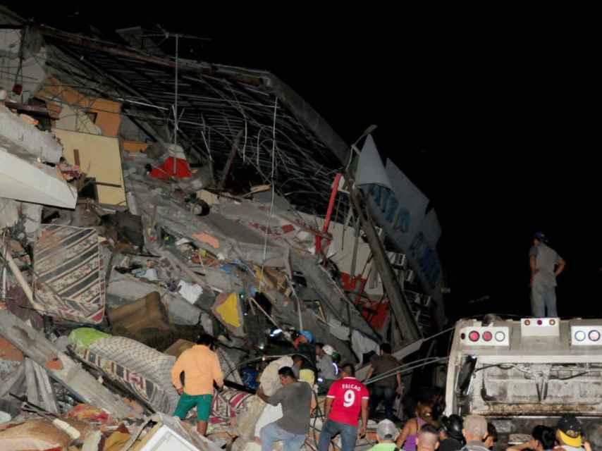 Varias personas buscan entre las ruinas de un edificio en la zona de Manta.