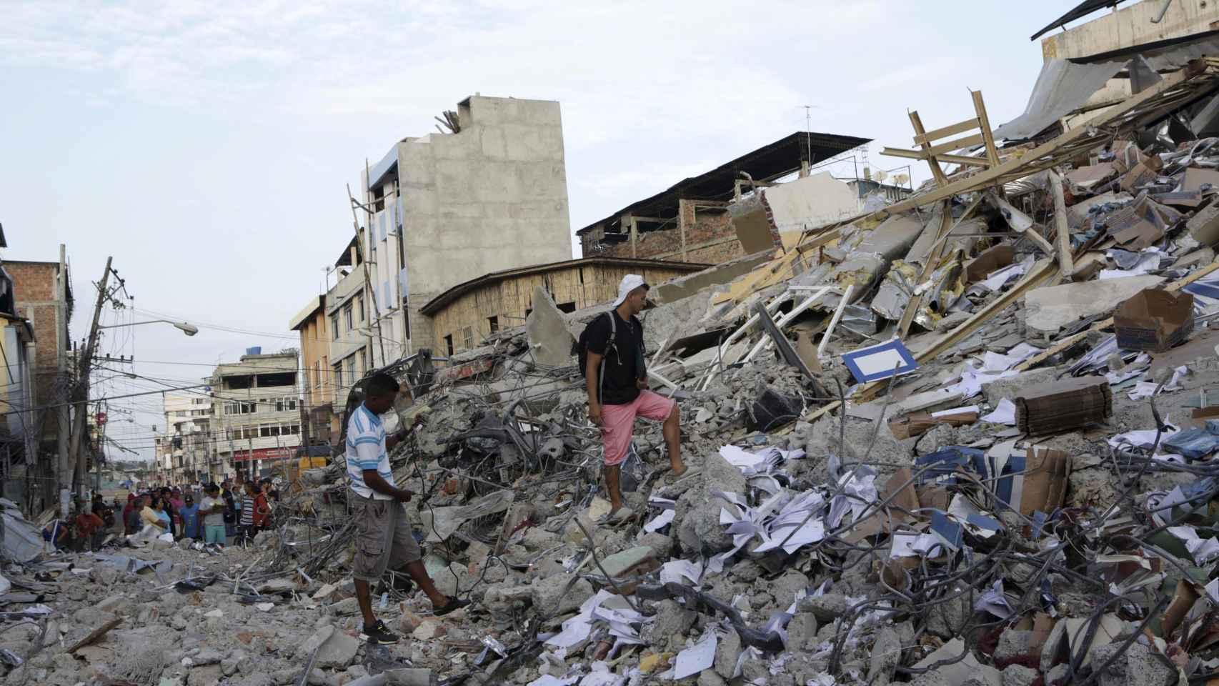 Los residentes de Portoviejo caminan entre las ruinas tras el seísmo.