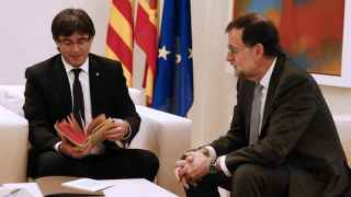 Puigdemont hojeando el regalo de Rajoy.