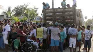 Personas reciben donaciones cerca del pueblo de Manta en Ecuador.