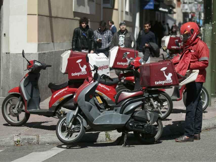 Un repartidor prepara su moto.