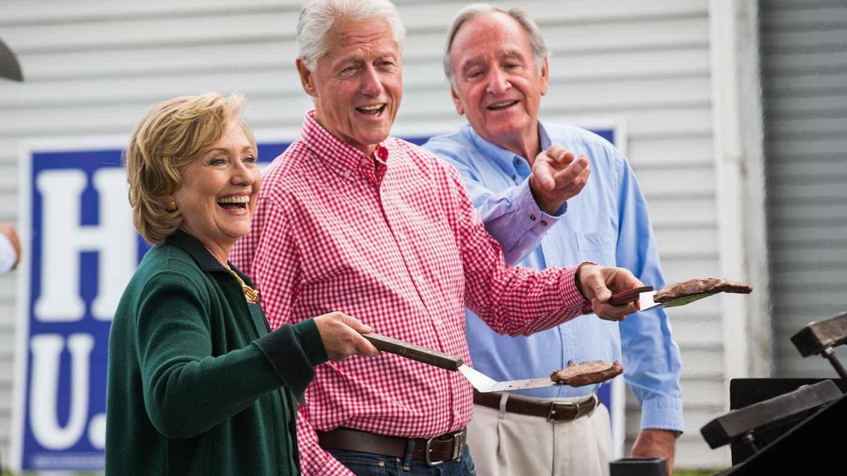 Bill Clinton y su mujer Hillary cocinando unas hamburguesas