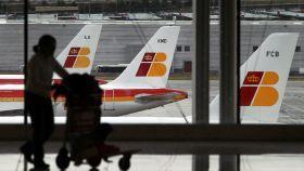 Un pasajero lleva su equipaje ante una hilera de aviones de Iberia. /