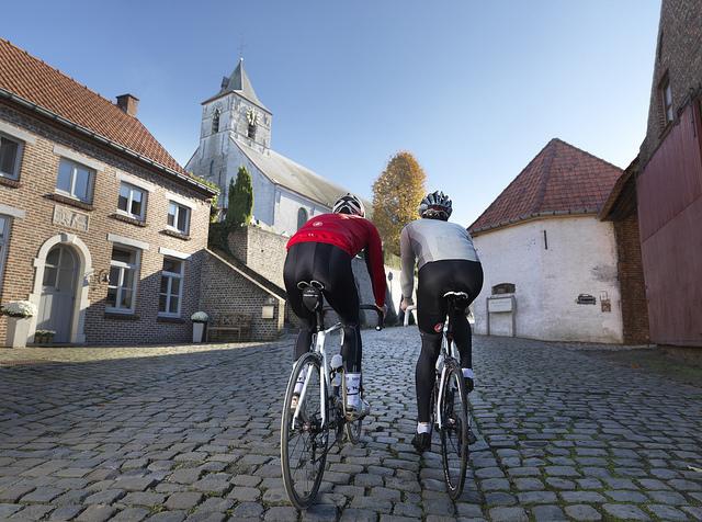 Dos personas practicando ciclismo por las calles de Flandes.