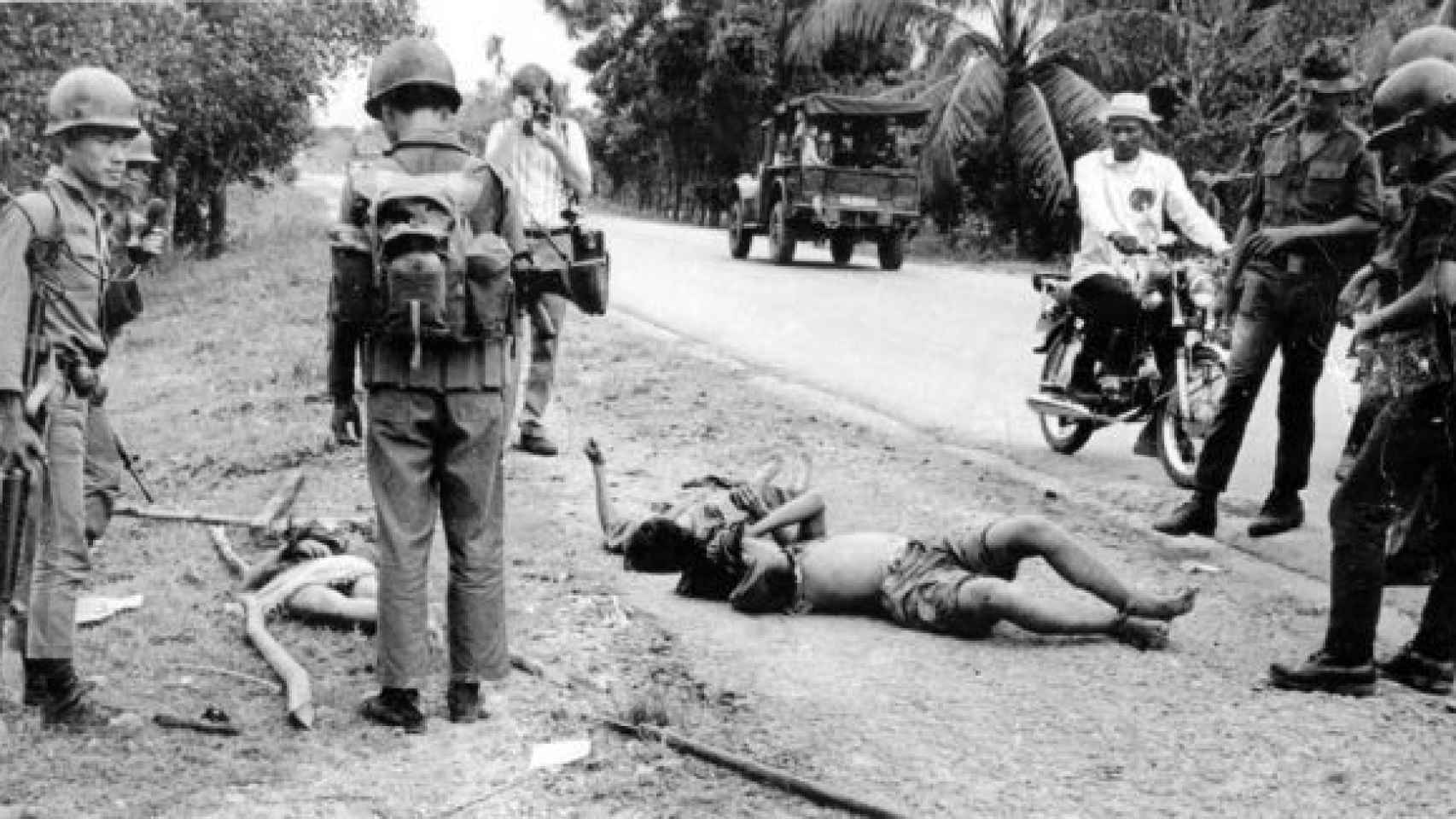 Múgica, fotografiando el cuerpo de un muerto durante la Guerra de Vietnam.