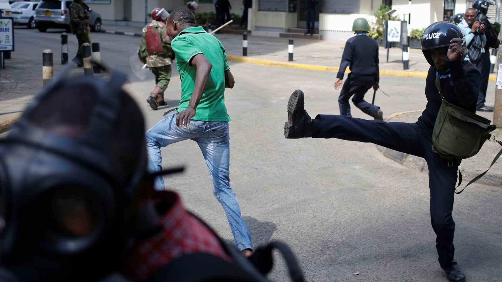 Un agente de los antidisturbios lanza una patada a los manifestantes