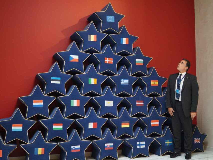 El ujier español observa la bandera de la Unión Europea presidiendo el Club de los 28.