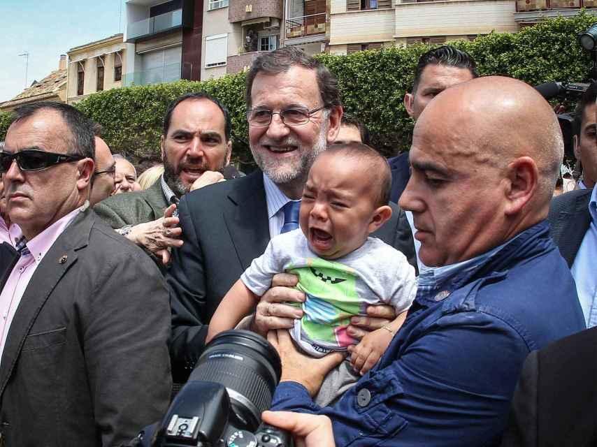 Un niño llora al hacerse una foto con Rajoy en Alfafar, Valencia.