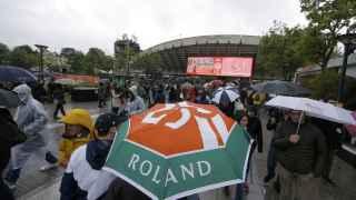Los aficionados pasan por Roland Garros con paragüas.