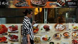 A woman checks her smartphone outside a restaurant at Tsim Sha Tsui shopping district in Hong Kong