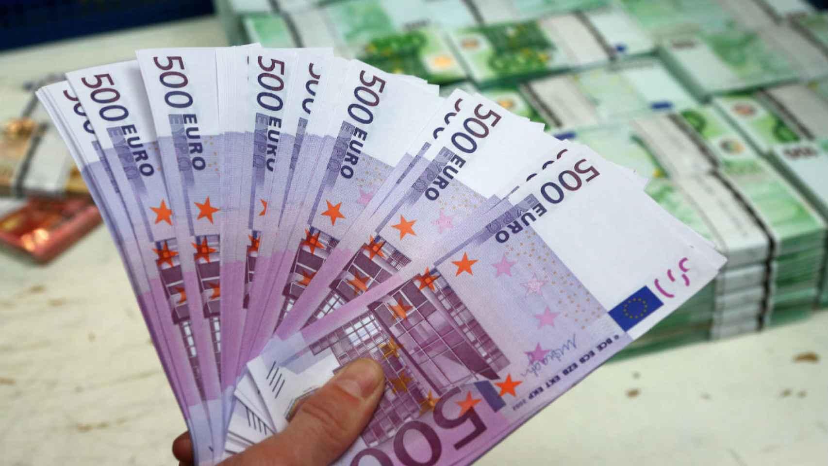 Un empleado de banca sostiene billetes de euro en Viena. /