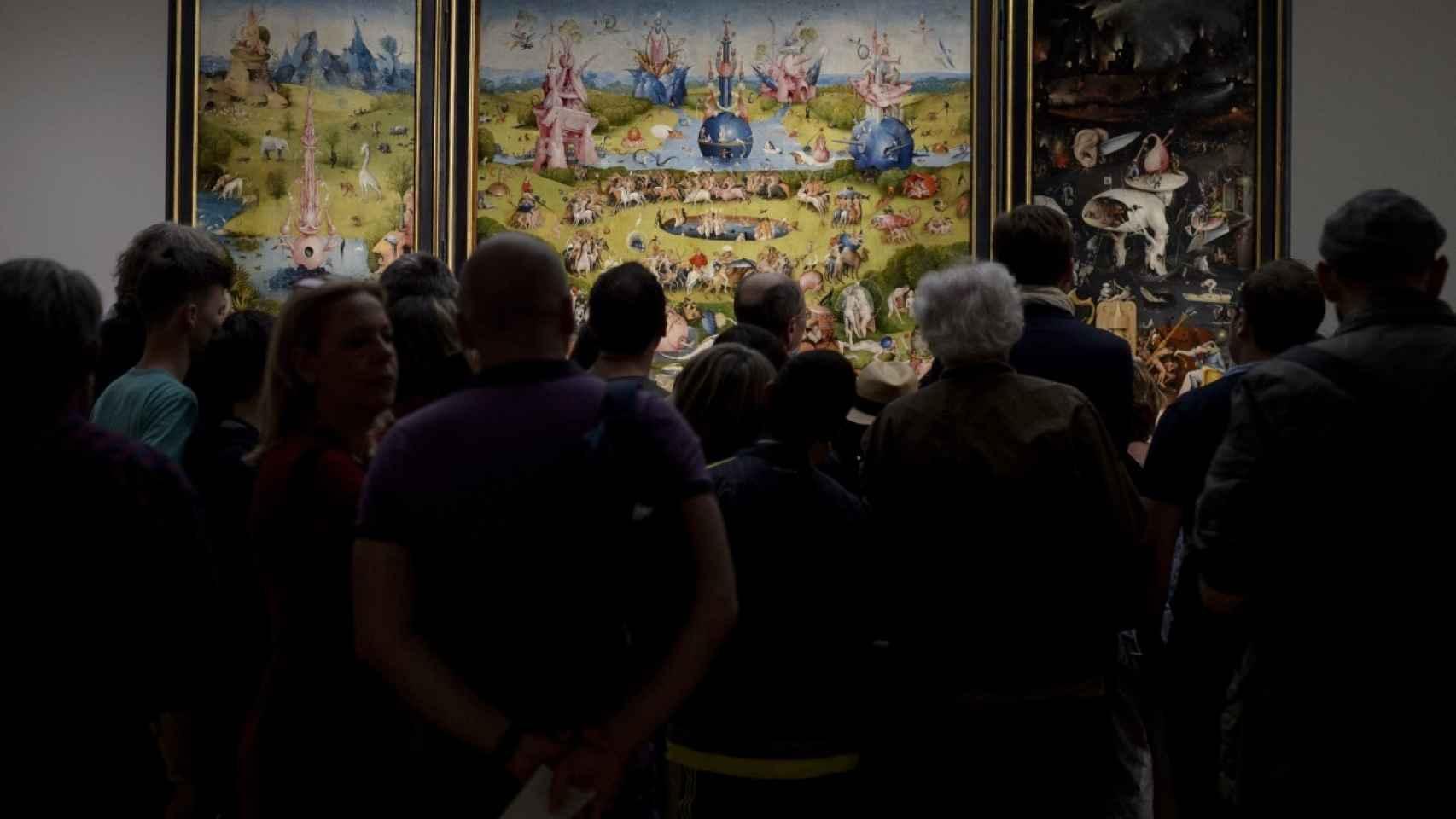 Visitantes amontonados frente al tríptico de El jardín de las delicias.